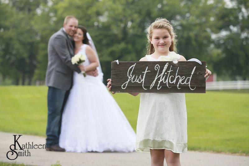 June wedding bride and groom with just hitched sign