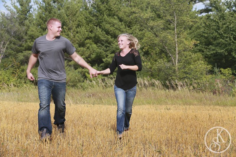 engagement couple running in field