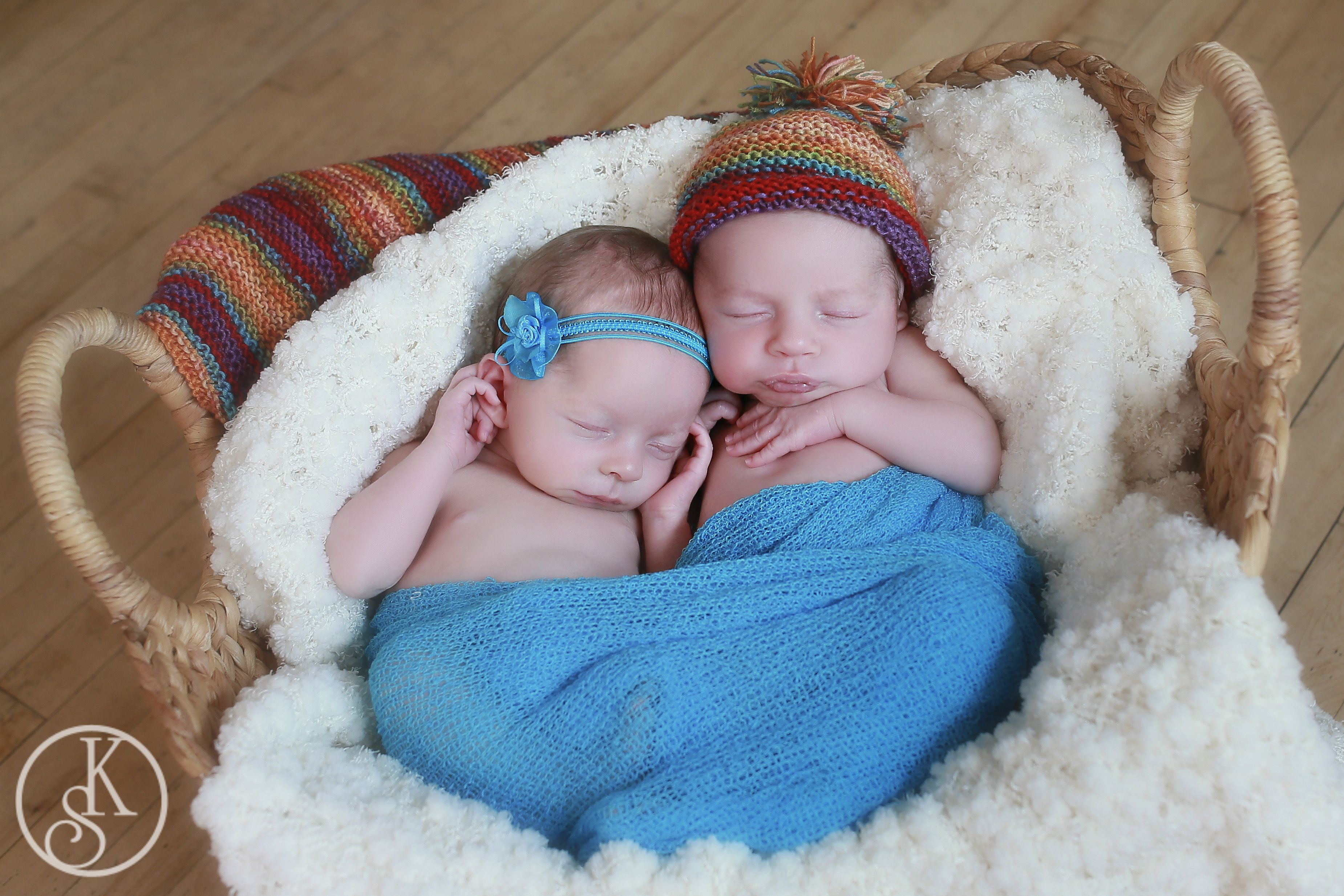newborn twins on location in basket with hat