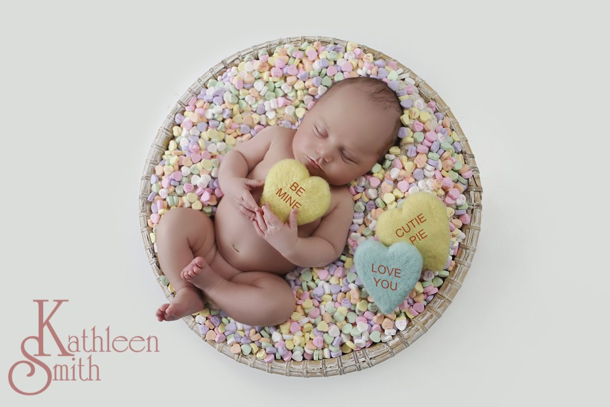 Baby in a basket of candy hearts
