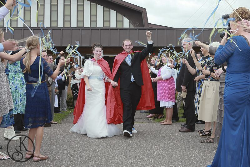 bride and groom wearing superhero capes