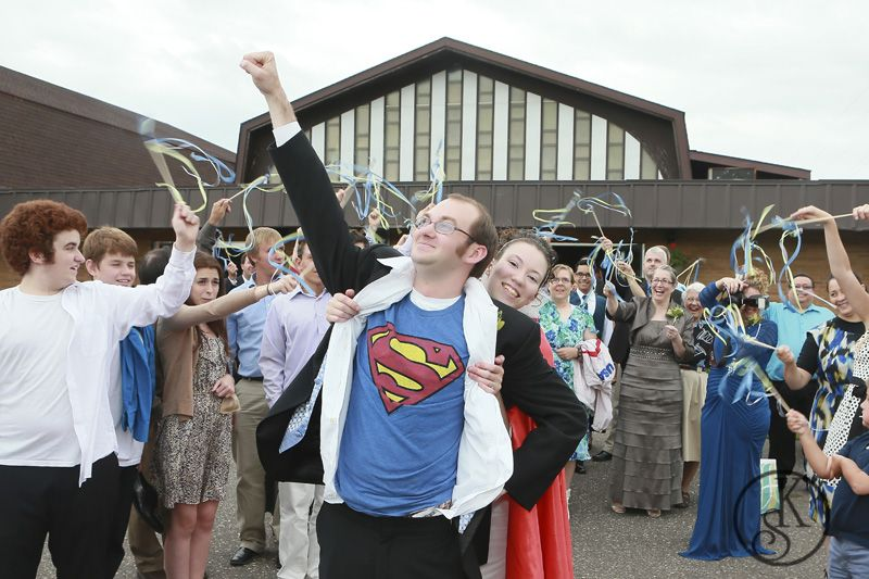 bride and groom wearing superhero capes leaving reception